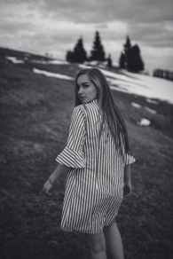 grayscale photo of woman in striped dress walking on hill slope with snow while looking back